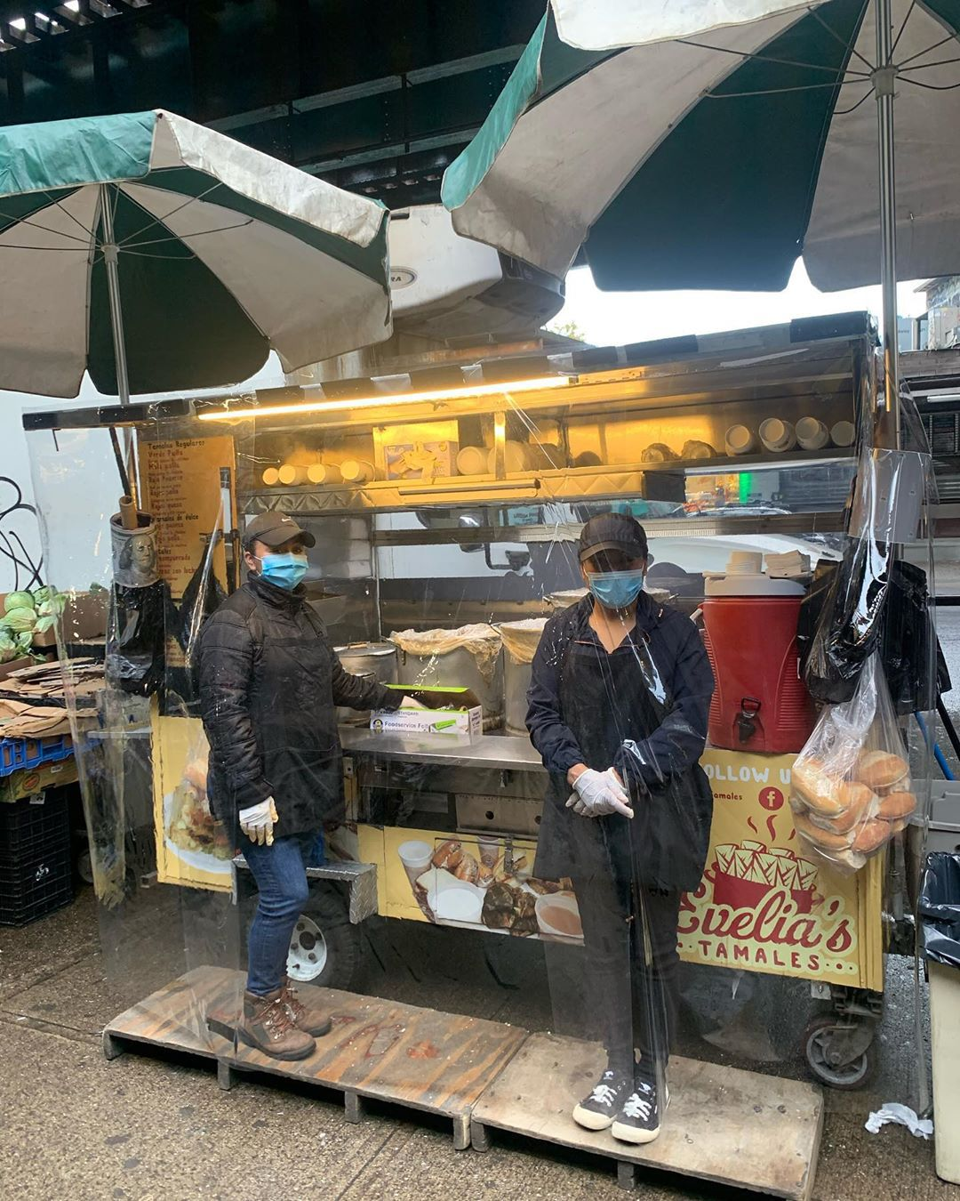 Two women stand in front of a food cart with masks on