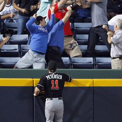 Miami Marlins left fielder Bryan Petersen (11) watches as fan battle for a ball hit for a home run by Atlanta Braves' Martin Prado (14) in the first inning of a baseball game in Atlanta, Wednesday, Sept. 26, 2012.