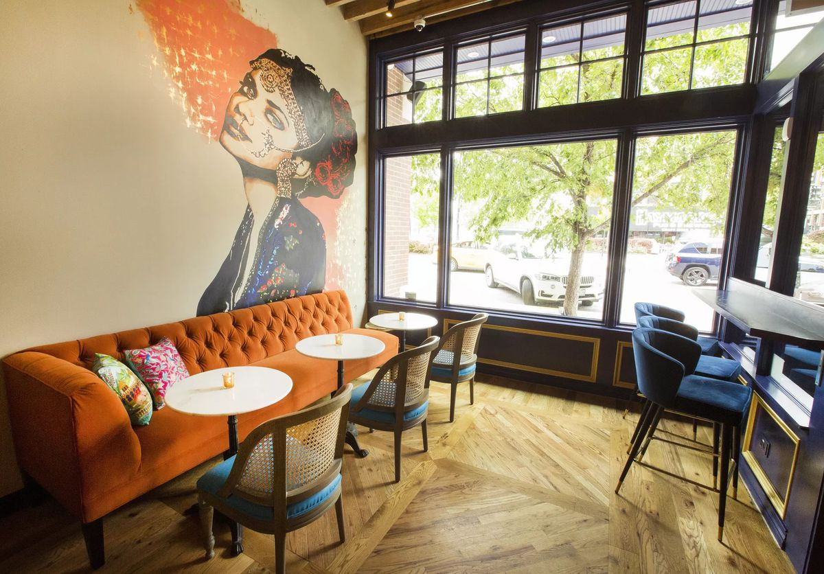 Rooh's dining room features high top seating, an orange couch, and a painted mural called Christine by Jenny Vyas,