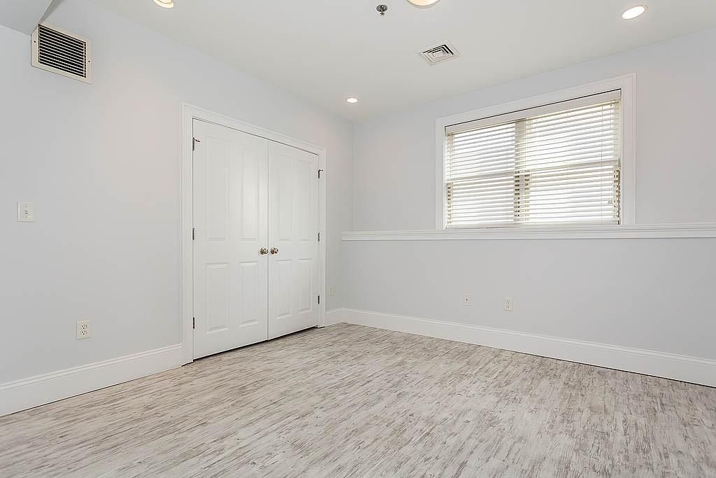 An empty bedroom with one window and a double-door closet.