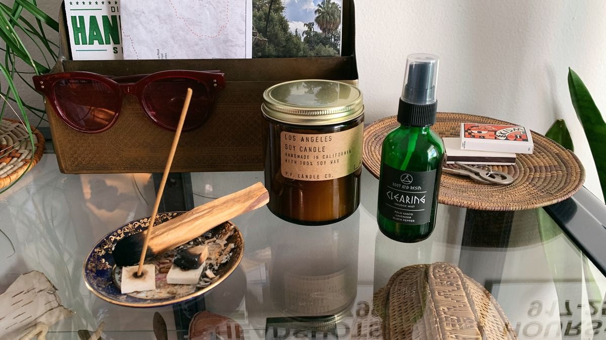 Several small items are positioned on top of a glass surface, including a mail holder, a pair of sunglasses, a candle in a brown jar, two wooden sticks, a spray bottle, and two matchboxes.