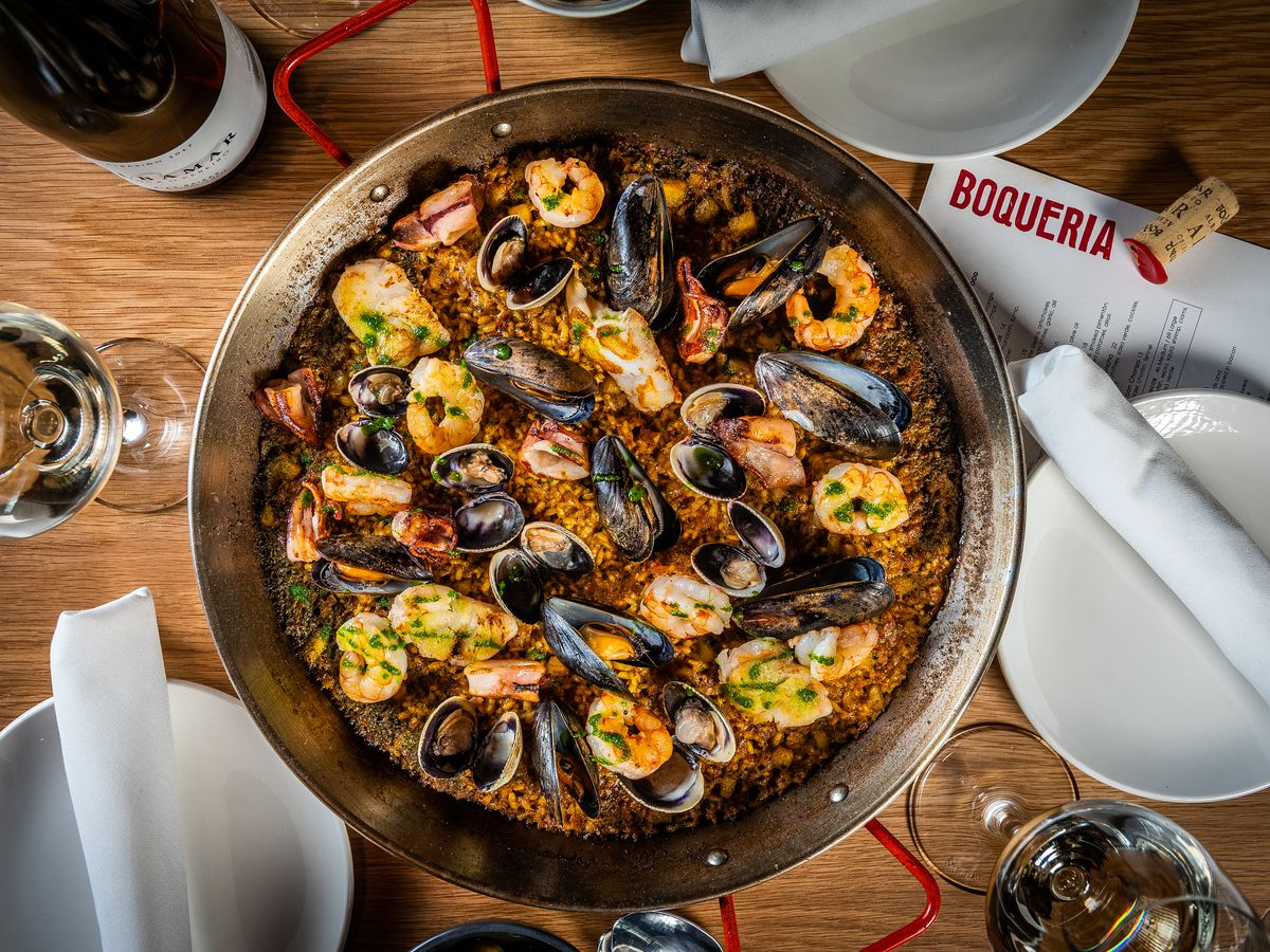 A large pan of paella for sharing, stuffed with rice, mussels, and shrimp in a cast iron pan.