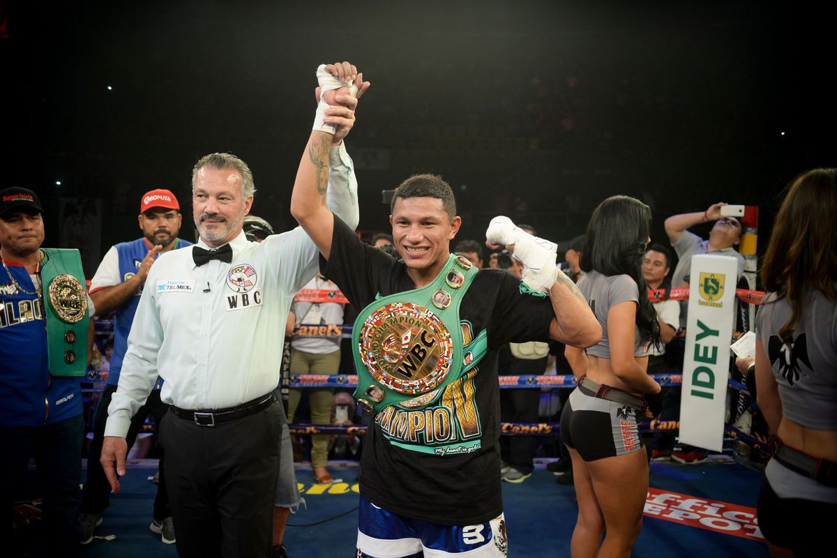 Mexico's Miguel Angel Berchelt (R) celebrates his win over Argentinas´ Jonathan Victor Barros (out of frame) in their WBC world super featherweight title boxing bout in Merida, Yucatan state, Mexico, on June 23, 2018.