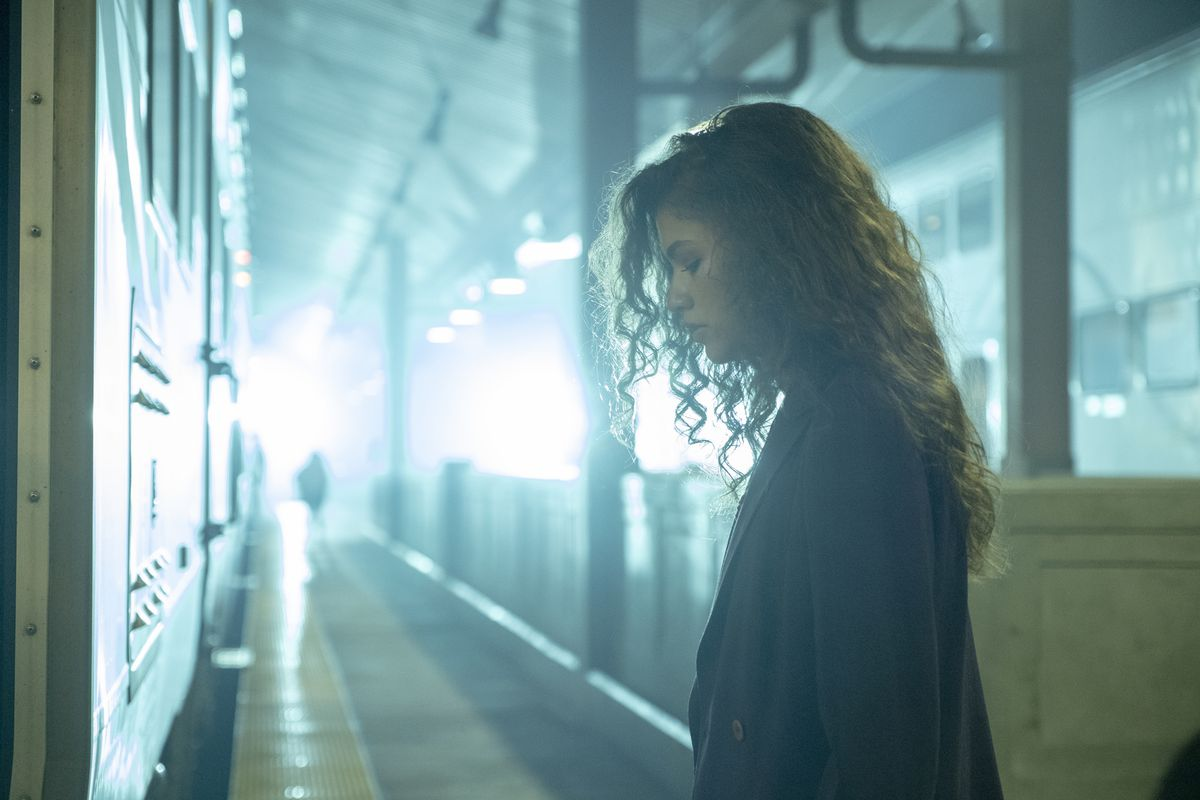 Zendaya as Euphoria's Rue stands in a train station looking mournfully down as the train pulls away.