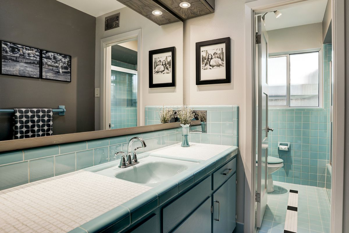 A vintage bathroom has teal cabinets and tile, with a large window, one sink, and a separate toilet room.