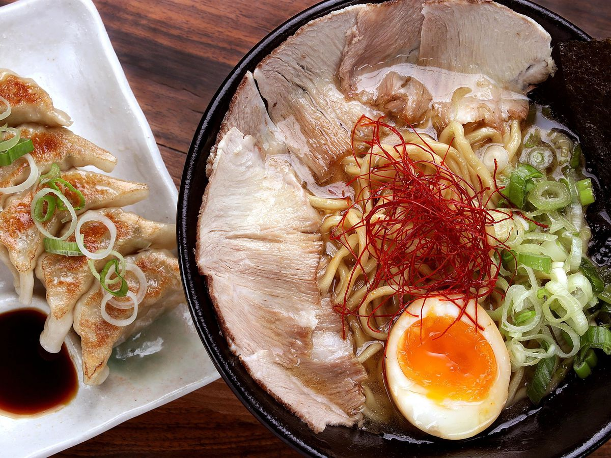 A bowl of ramen topped with slices of pork, egg, and scallion, beside a plate of gyoza with dipping sauce