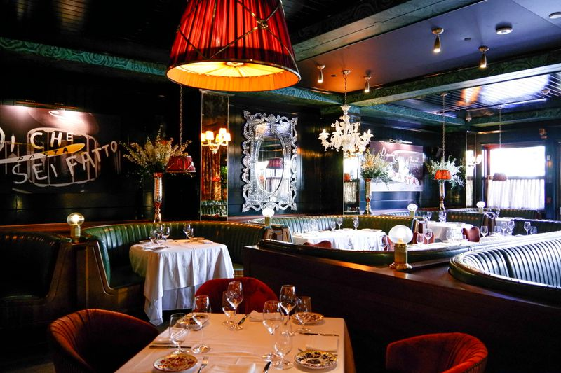 A dimly lit dining room with white tablecloth-covered tables and green booths
