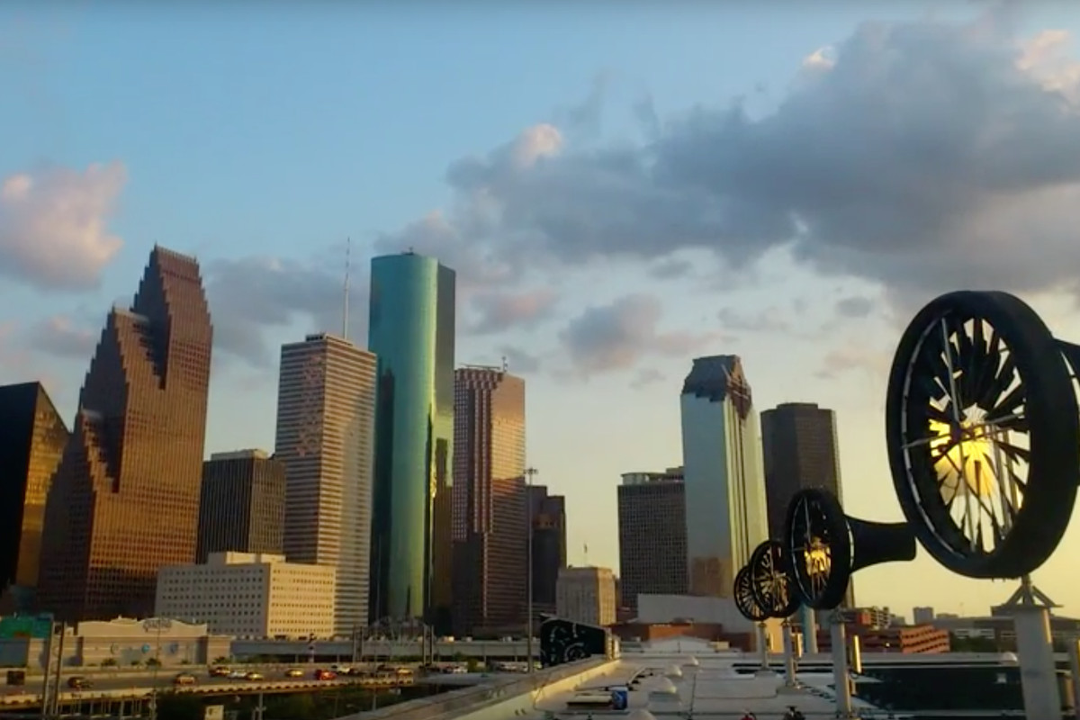 Wind turbines on a roof with the skyline of Houston in the background