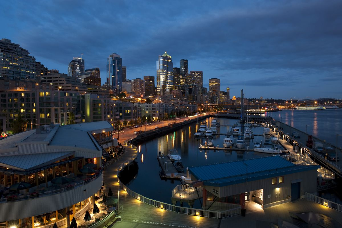 A view of Seattle's skyline near the pier, overlooking the Puget Sound at night
