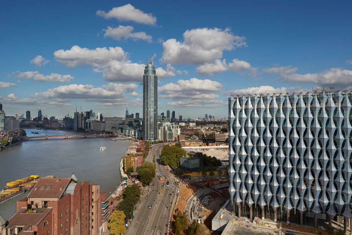 Cuboid glass building sheathed in faceted solar shading panels rises by the river in London.
