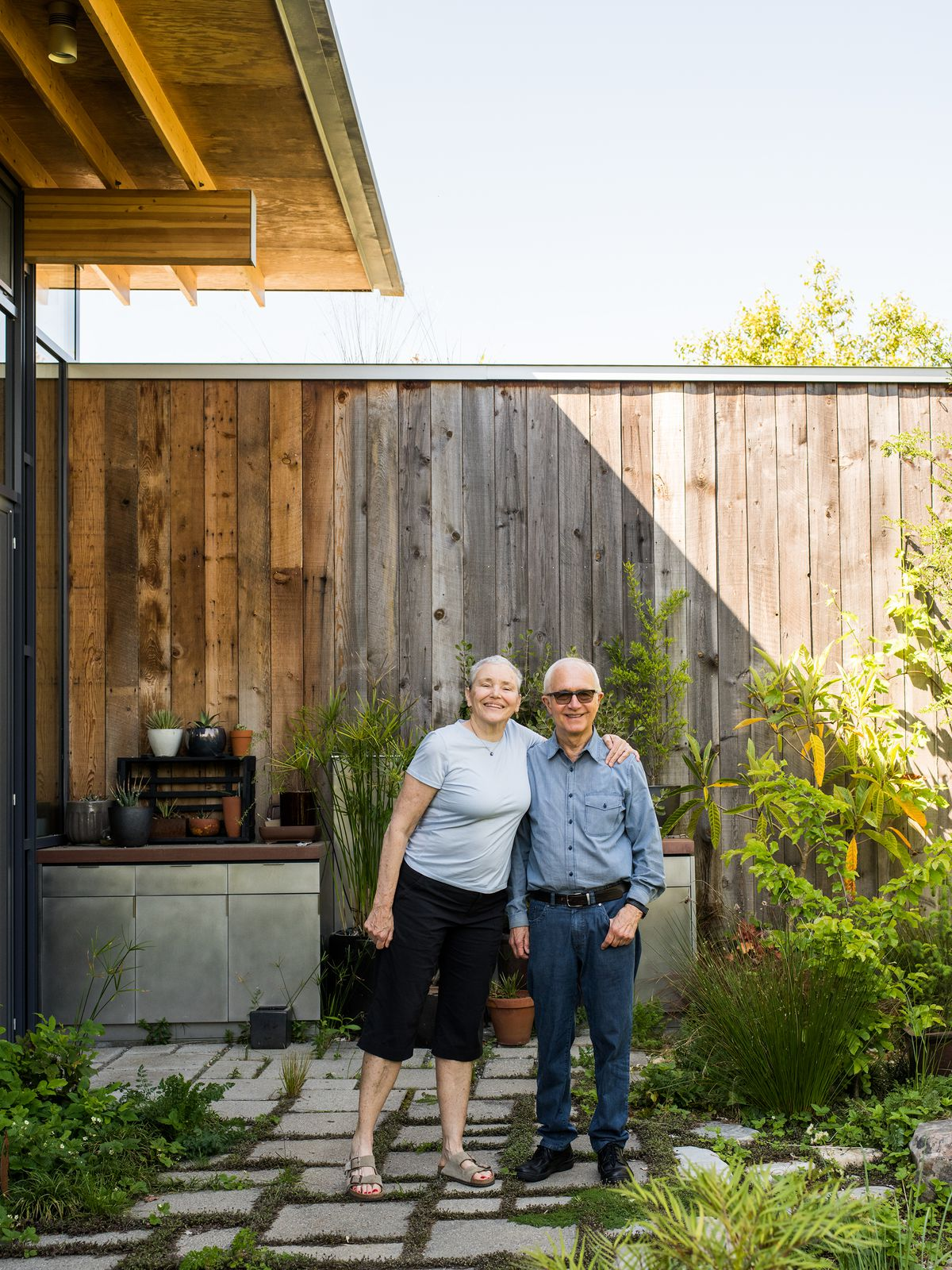 Two people, a man and a woman, are standing outside.  Behind them is a tall wooden fence and plants next to the outside area they stand on.