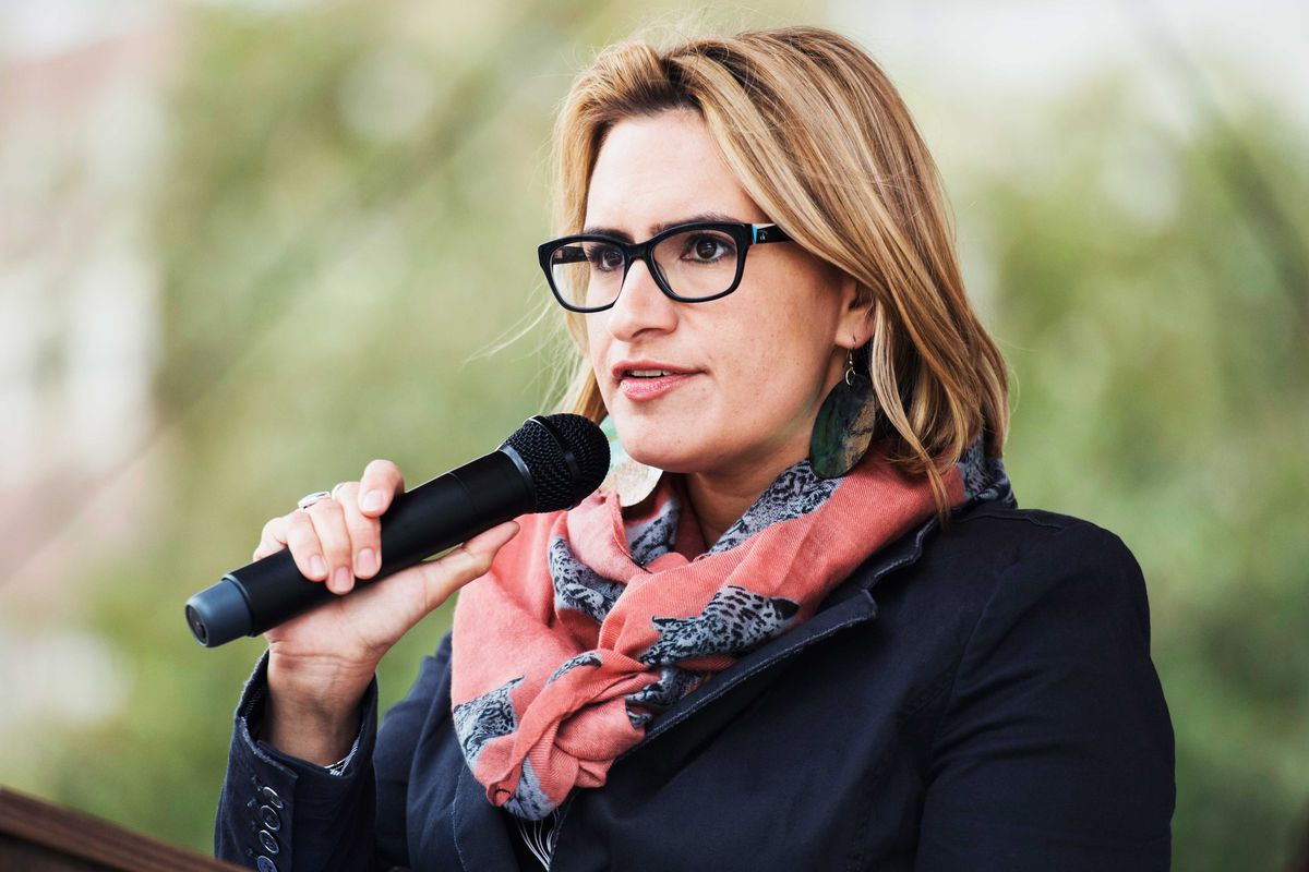 Peggy Flanagan holds a microphone while speaking outdoors.