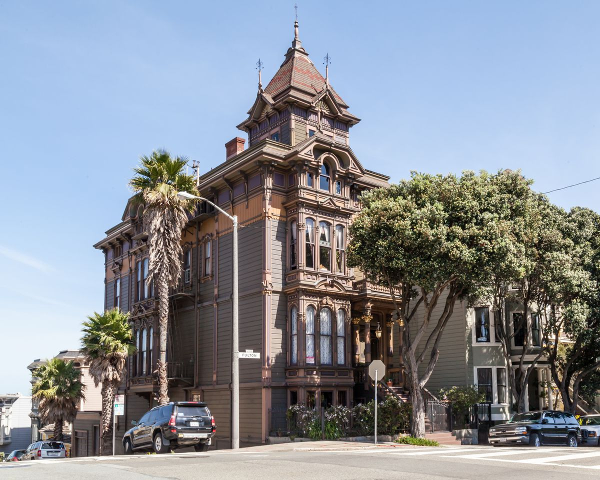 The exterior of a house in San Francisco. The facade is brown with a tall tower on top. There are trees surrounding the house.