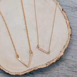 """Phyllis + Rosie Mini V-Bar Necklace, <a href=""""http://shop.thistleclover.com/collections/necklaces/products/phyllis-rosie-mini-v-bar-necklace"""">$110</a>; Blanca Monros Gomez Dainty Diamond Horizontal Bar Necklace, <a href=""""http://shop.thistleclover.com/coll"""