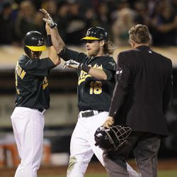 Oakland Athletics' Josh Reddick, center, is congratulated after hitting a grand slam off Boston Red Sox's Mark Melancon in the seventh inning of a baseball game Friday, Aug. 31, 2012, in Oakland, Calif.