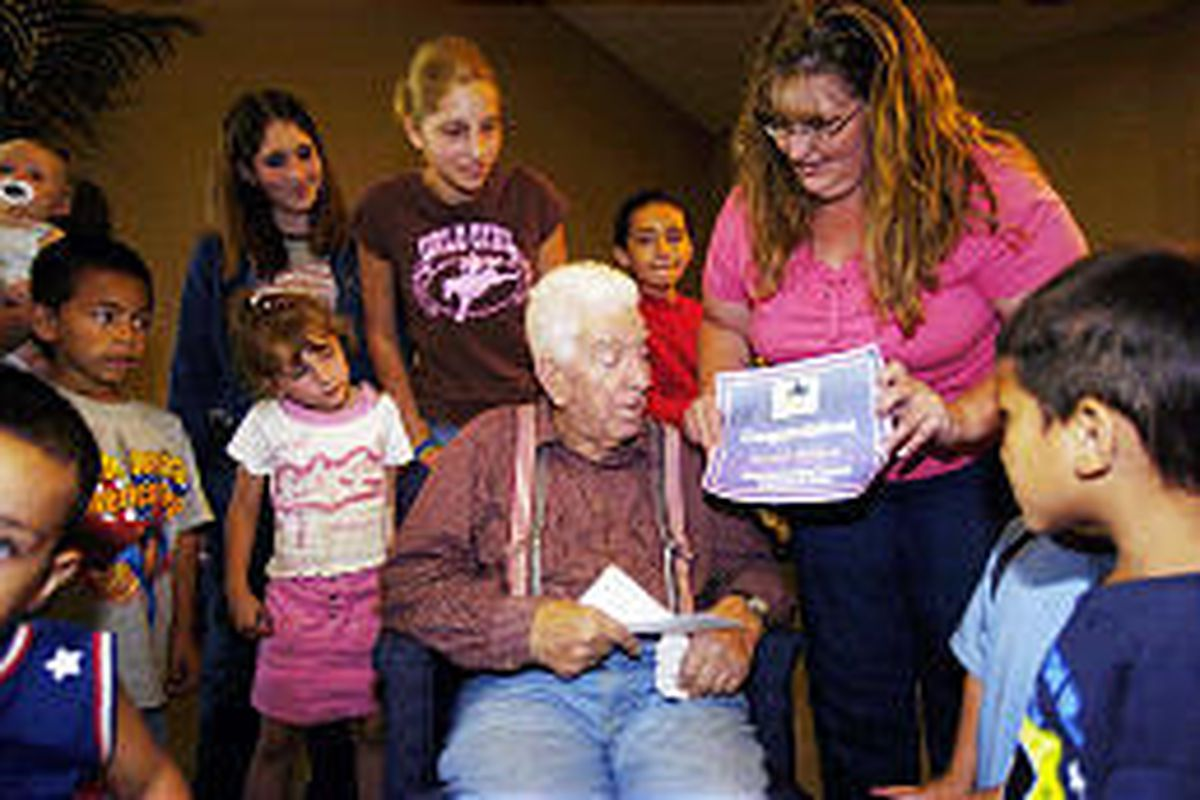 Homer C. Whitlock receives an award for the most grandchildren in Utah from granddaughter Lori Bailey as other family members look on.
