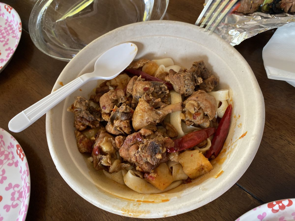 Dapanji, or big plate chicken: a takeout container of bone-in chicken pieces over handmade noodles
