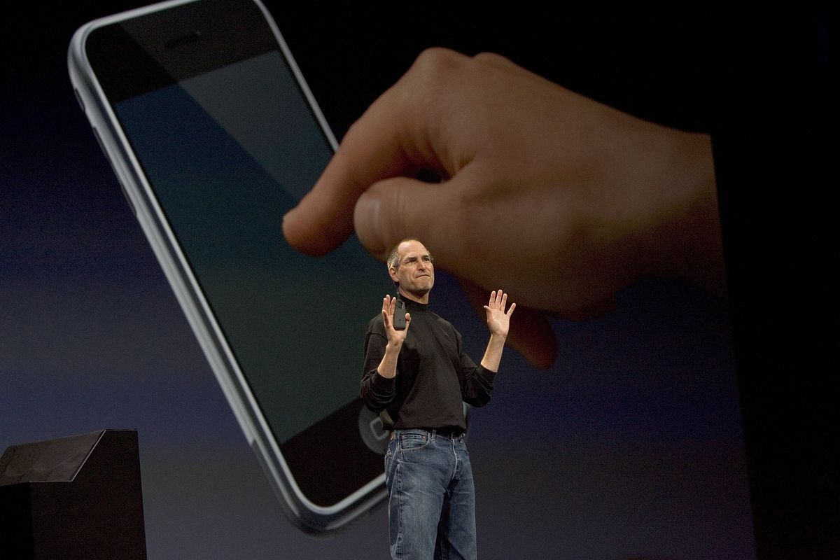 Steve Jobs onstage in front of a picture of a hand touching an iPhone screen.