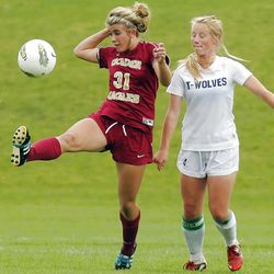 Maple Mountain's #31 McKell Nielsen, left, kicks the ball away from Timpanogos' #4 Lizzy Jessop during play Tuesday, Sept. 25, 2012. Maple Mountain won 2-1.