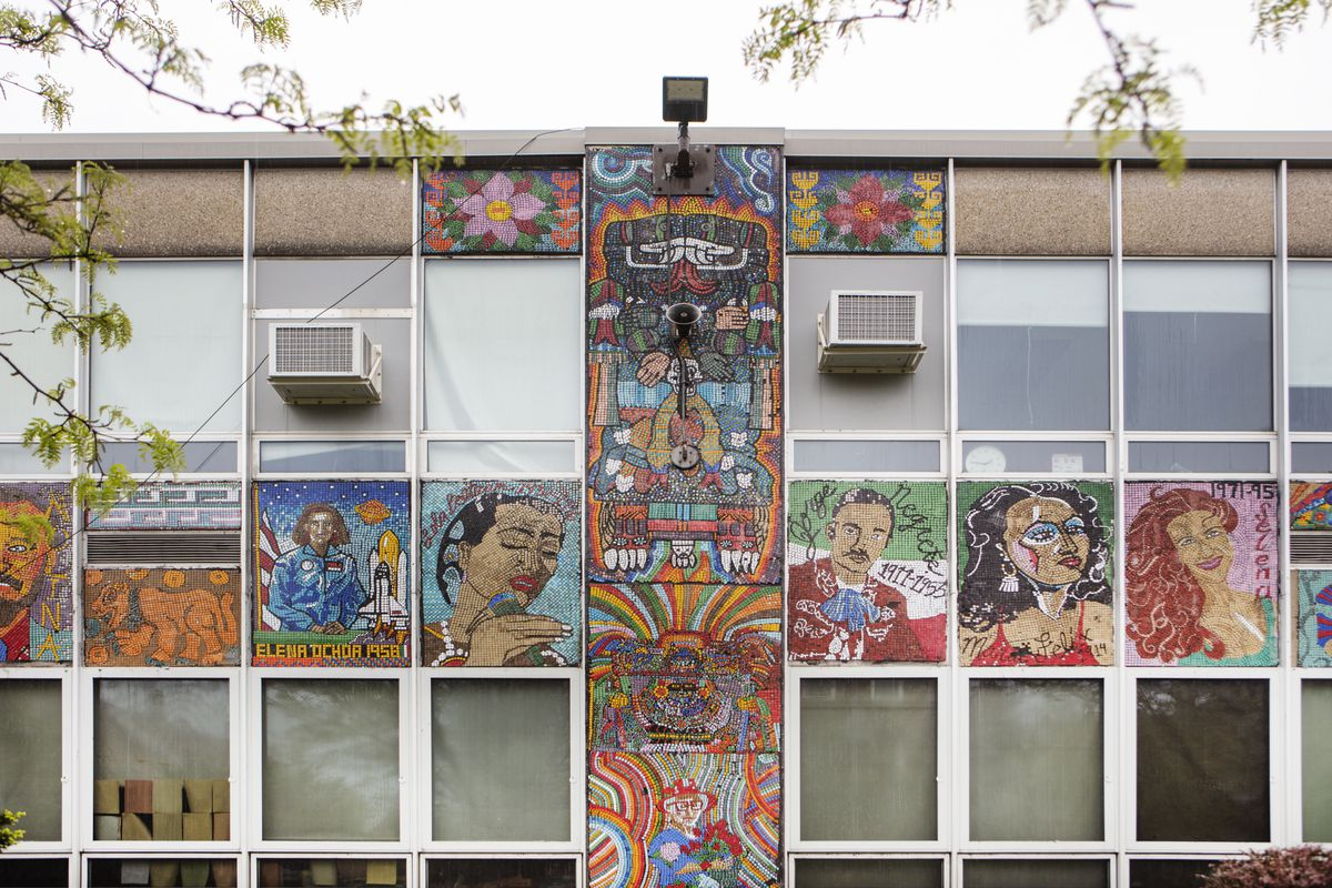 The exterior of a building. There are multiple windows. There are also colorful murals of various people in between some of the windows.