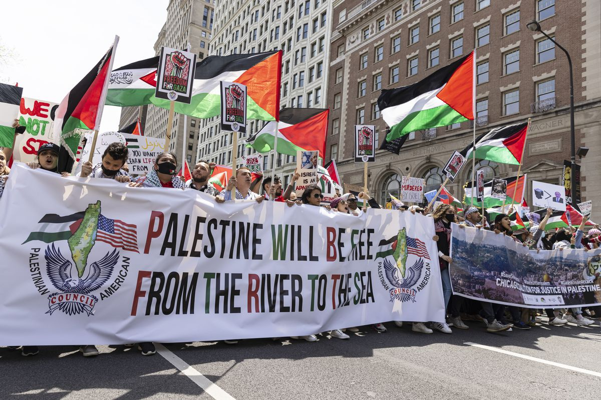 Supporters hold up flags and posters during a rally and march in support of Palestinians in the Loop in response to an ongoing assault between Israelis and Palestinians in the middle east, Sunday, May 16, 2021.