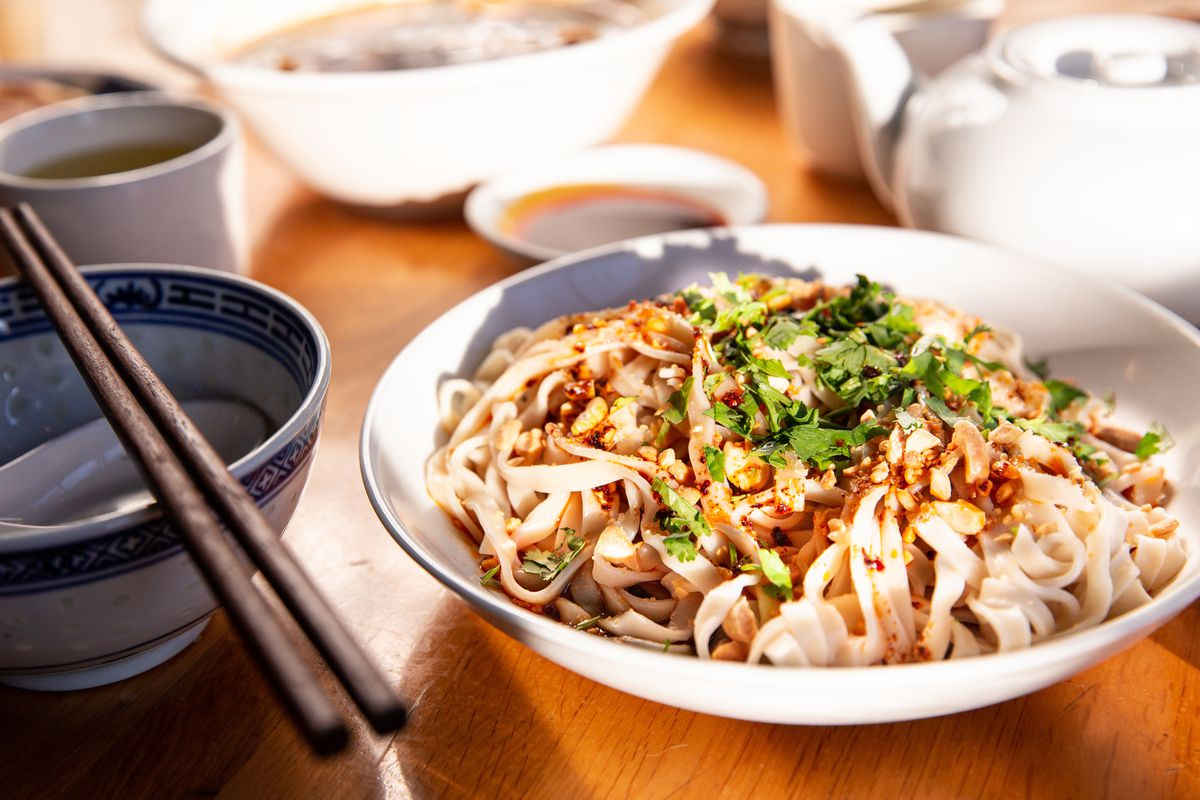 A blow of noodles topped with cilantro and peanuts.