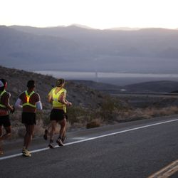 Oswaldo Lopez (C) of Madera, California and Carlos Alberto of Portugal (R) run wearing headlamp near Panamint Springs as night falls during the AdventurCORPS Badwater 135