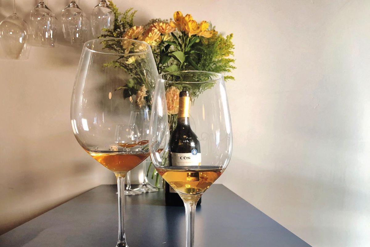 Two glasses of orange wine in front of a vase of flowers.