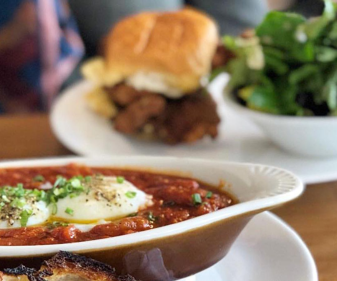 An oval dish of shakshuka all'amatriciana, with some other brunch dishes visible in the background