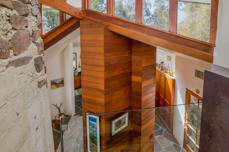 Overhead view of a column of redwood beams under clerestory windows.