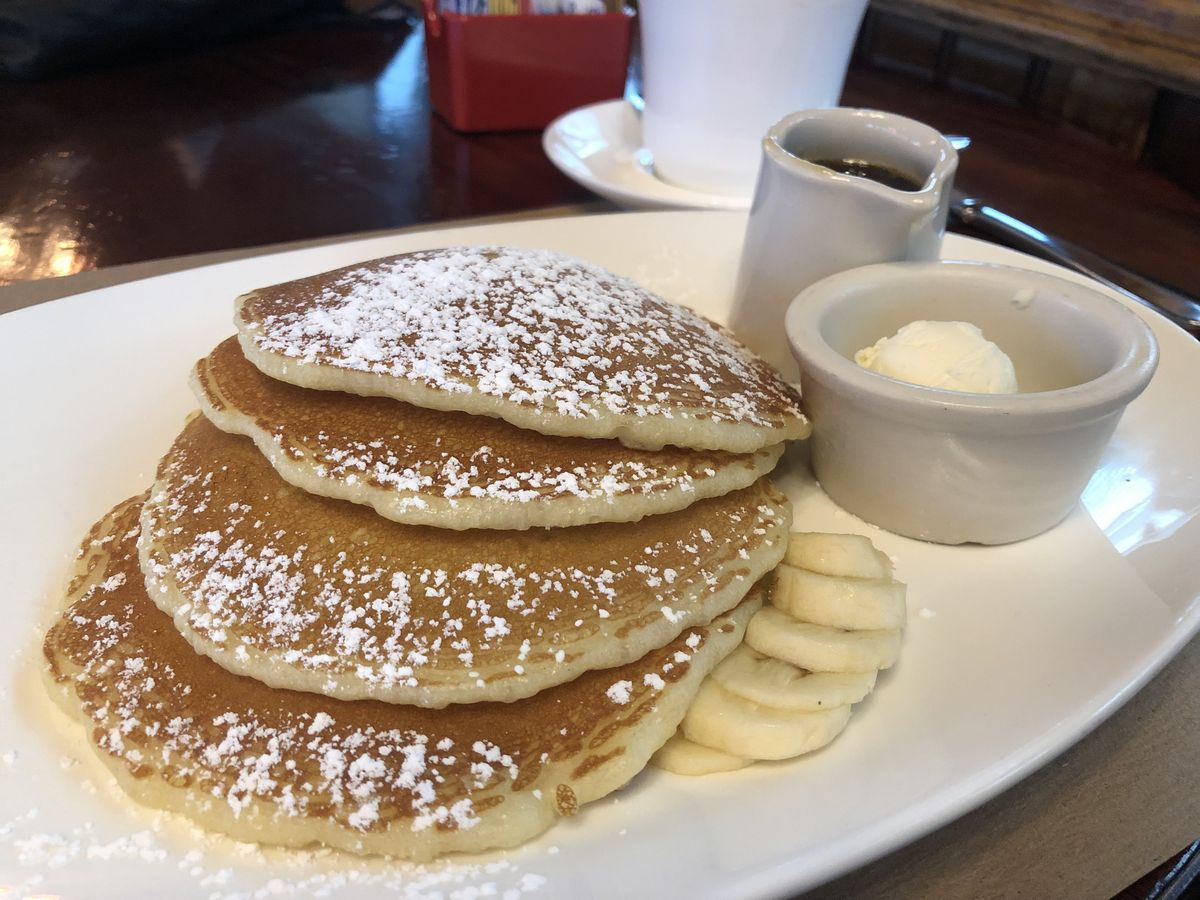A stack of banana pancakes sits on a white plate, with sides of maple syrup and butter.