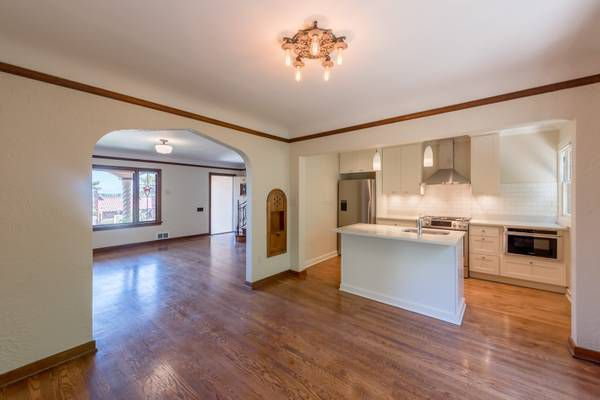 A living area separated from another living area by an arch, with a kitchen in a large alcove