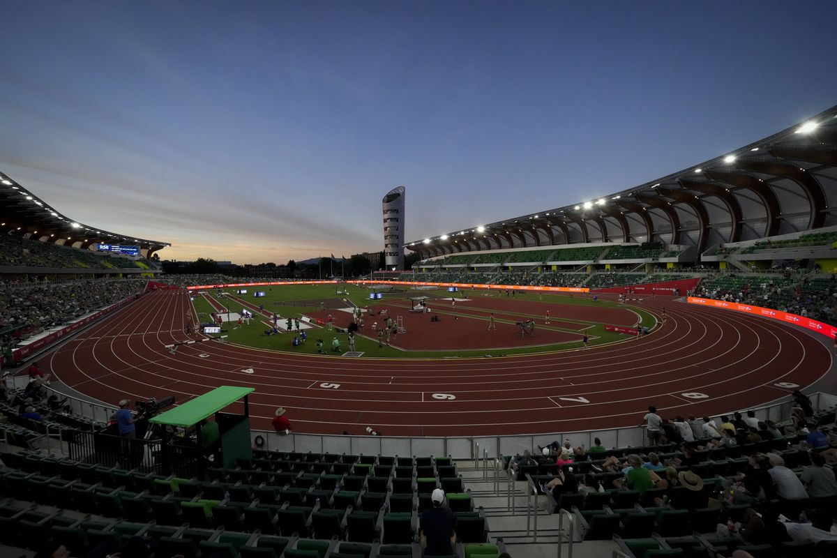 Runners compete on the track at dusk