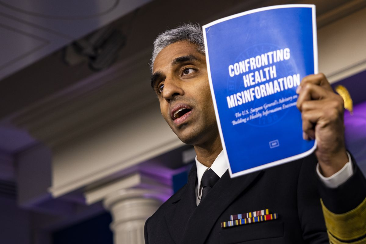 """Vivek Murthy, the US surgeon general, speaks during a news conference and holds up a piece of paper that says, """"confronting health misinformation."""""""