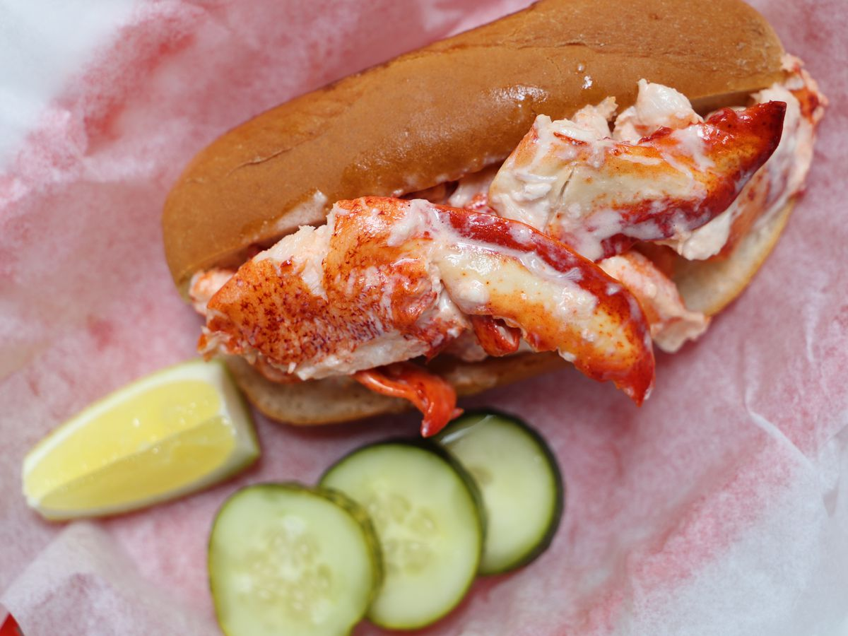 lobster roll with lemon wedge and pickle slices