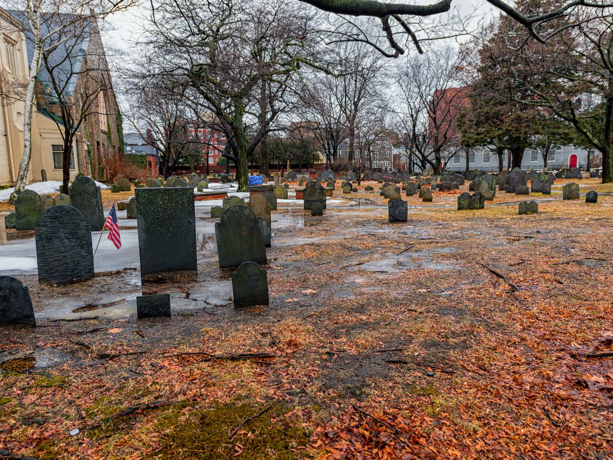 Rows of headstones amid a soggy, leave-covered lawn.