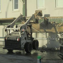 3:22 p.m. The bobcat's front wheels come off the ground, as it brings down the ticket window overhang -