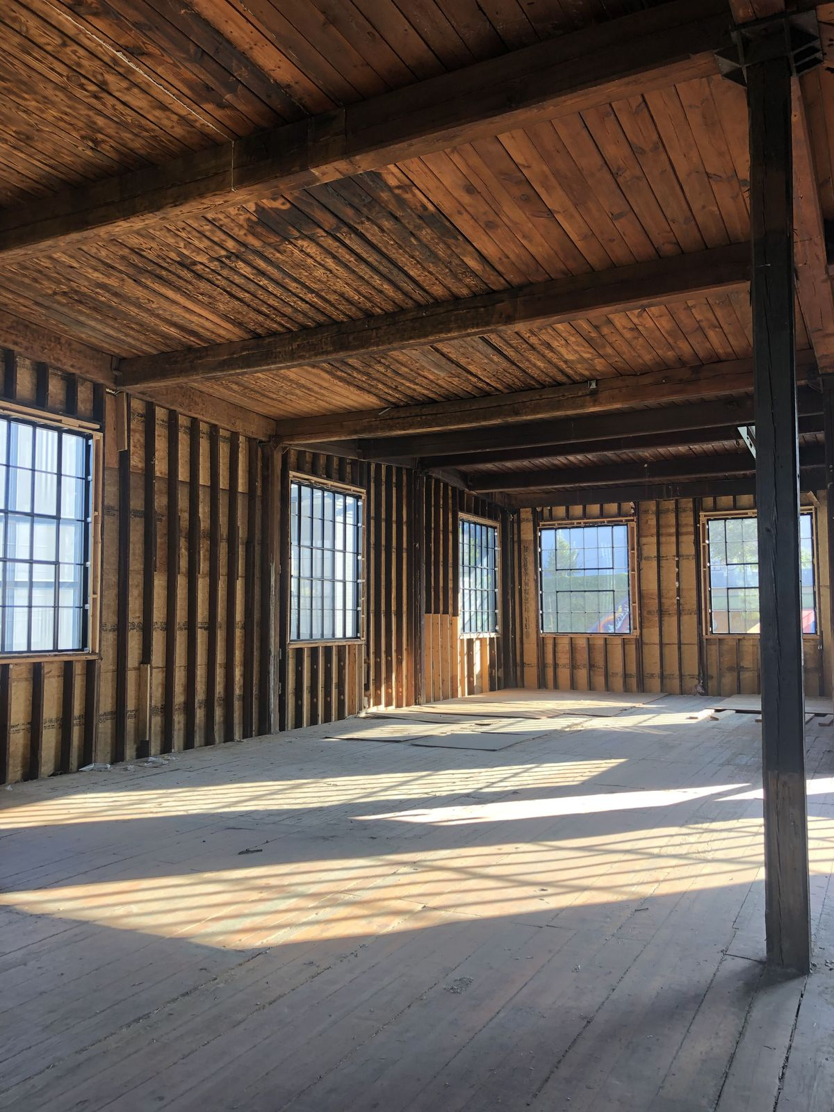 A photo of the building's interior shows old, raw wood and large windows.