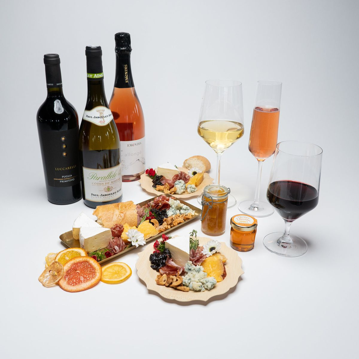 A charcuterie board with cured meats and cheeses is surrounded by three bottles of wine and three glasses.
