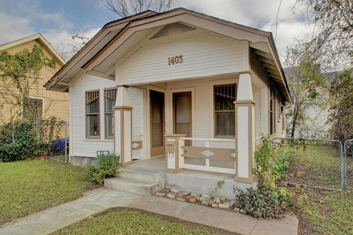 A small, sort of Craftsman wood-frame home with front porch and small yard, house is beige/off-white