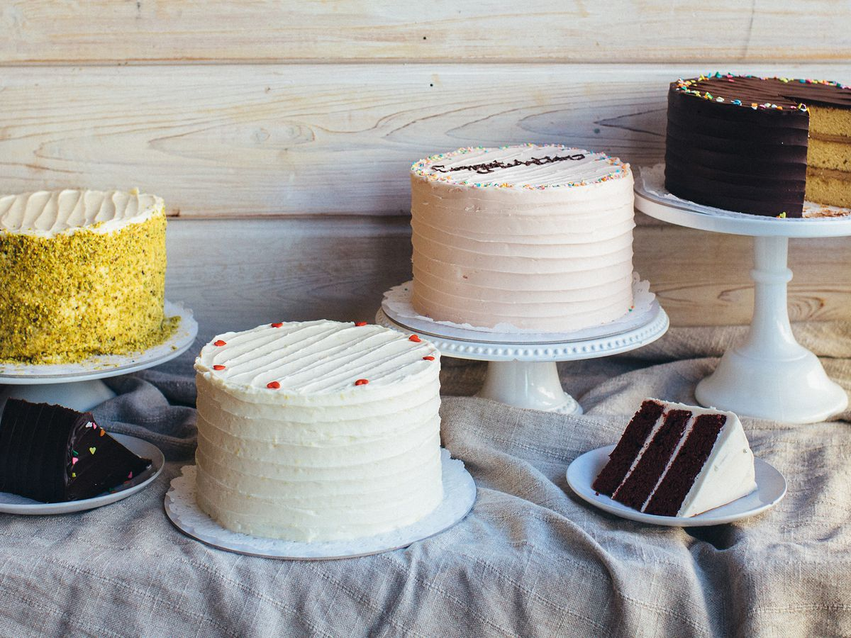 Four cakes, three of them on cake stands, with one coated in pistachio, two with white icing, and a cut chocolate cake