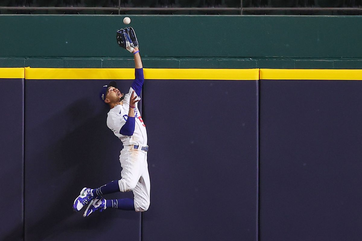 Mookie Betts #50 of the Los Angeles Dodgers catches a fly ball at the wall on a hit by Freddie Freeman (not pictured) of the Atlanta Braves during the fifth inning in Game Seven of the National League Championship Series at Globe Life Field on October 18, 2020 in Arlington, Texas.