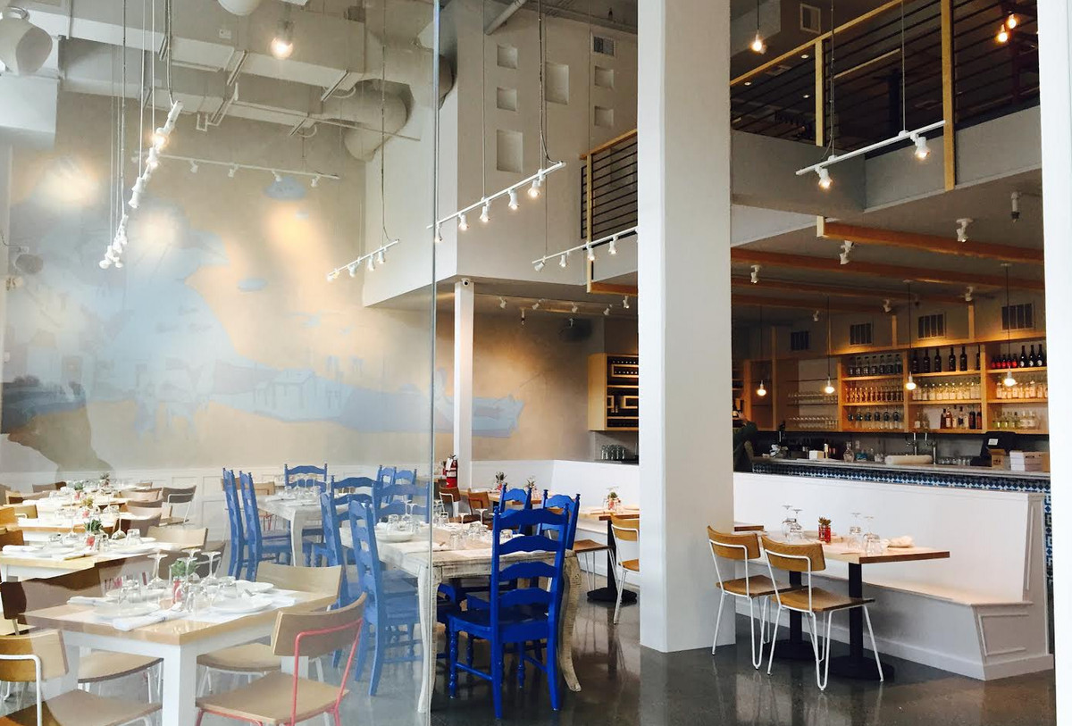 The bright blue and white dining room of Omega Ouzeri in Capitol Hill.