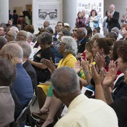 The audience at the California African American Museum in Los Angeles applauds on Friday, June 19, 2015, during a news conference announcing the Freedmen's Bureau Project.