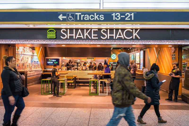 The exterior of a Shake Shack burger restaurant in a train station. People walk past the exterior.