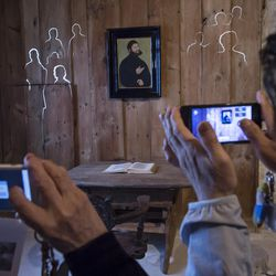 Japanese tourists shoot photos of a video installation in the historical Luther room, where Martin Luther translated the Bible, during a press preview of the national special exhibition 'Luther and the Germans' at the Wartburg Castle, where Martin Luther translated the New Testament to German, in Eisenach, Germany, Tuesday, May 2, 2017. The exhibition presents around 300 exhibits from the Wartburg Foundation collection or on loan from other German and international institutions. The exhibition starts on May 4, 2017 and lasts until Nov. 11, 2017. (AP Photo/Jens Meyer)