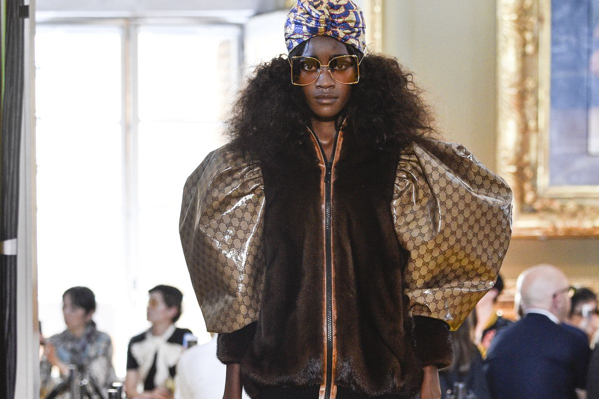 A model walks the runway wearing a fur jacket with shiny Gucci logo sleeves.