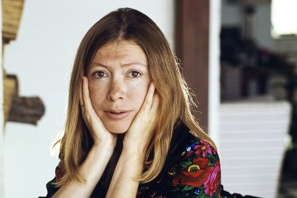 A portrait of Didion with her hands cradling her face.