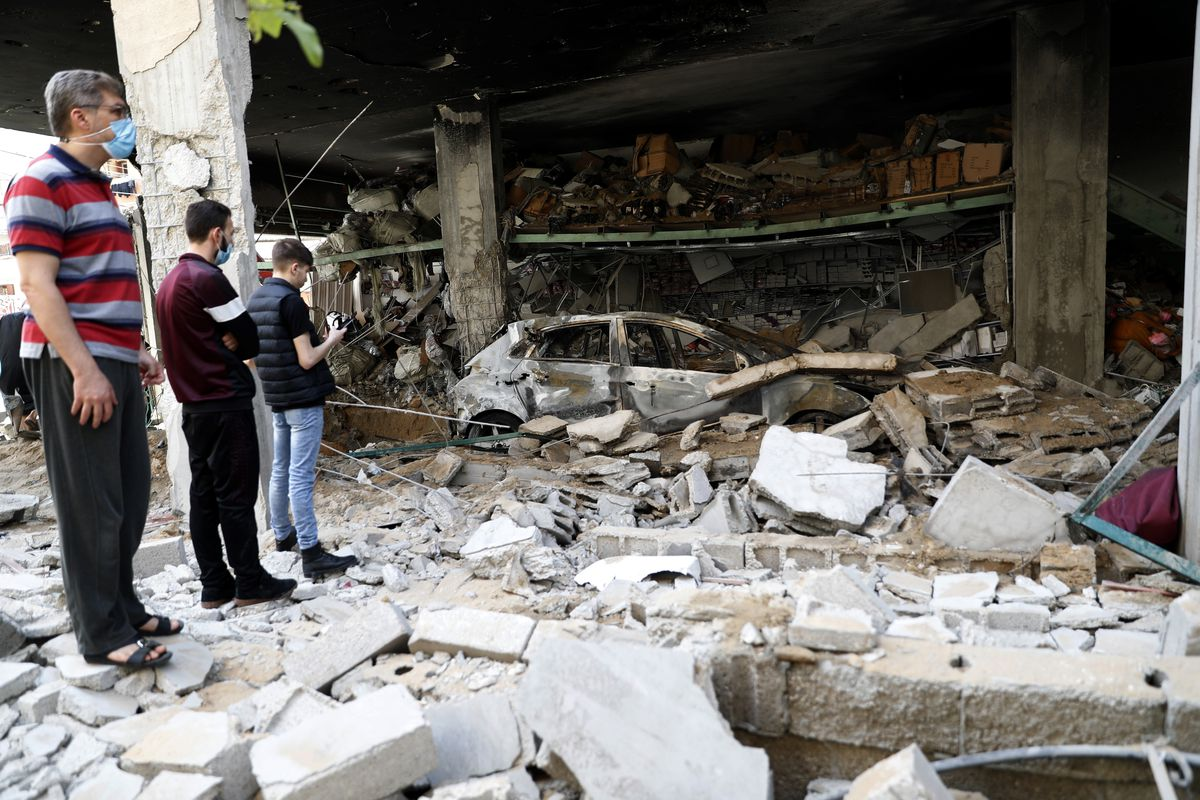 People inspect the rubble of destroyed residential building which was hit by Israeli airstrikes, in Gaza City.