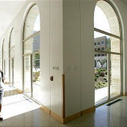 A student walks down a hallway in the Joseph F. Smith Building, which features an enormous courtyard.